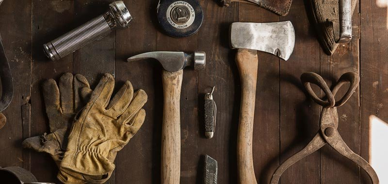 Hammer, axe, and gloves on a wooden table
