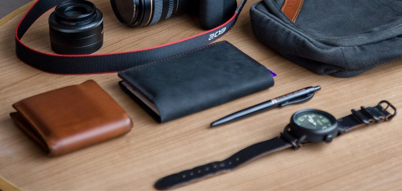 Wallets, pen and watch on wooden desk