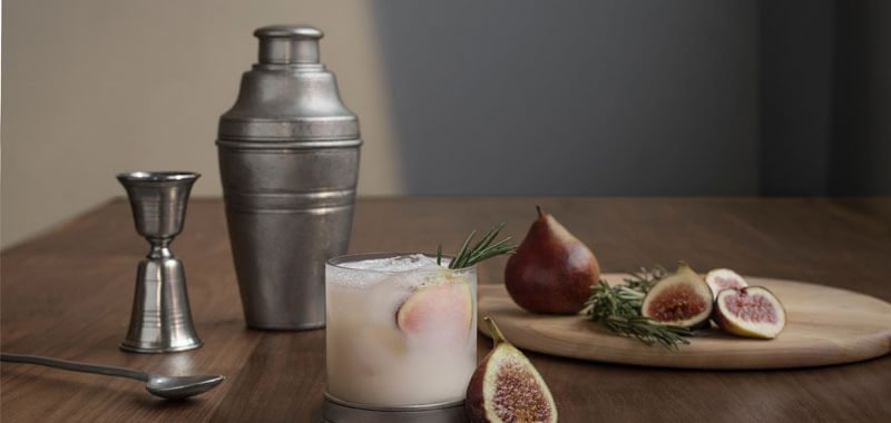 Cocktail shaker on table with jigger, fruit and a glass