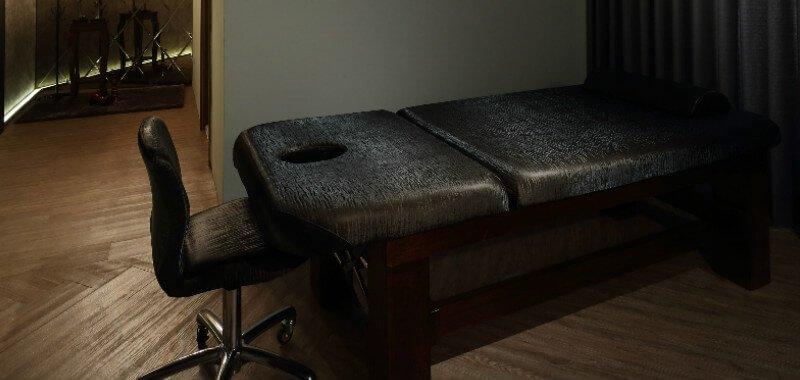 Gray massage table on wooden floor