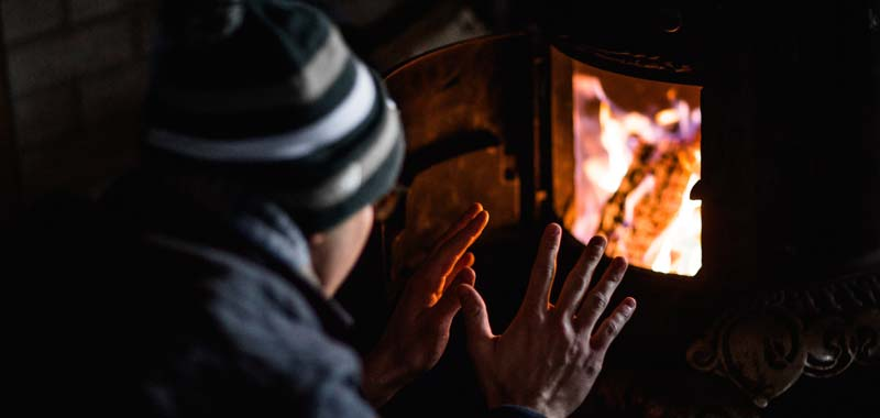 Man with hands up to lit fireplace