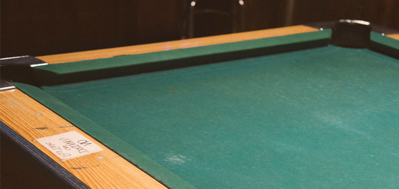 Empty snooker table with green cloth and wooden sides